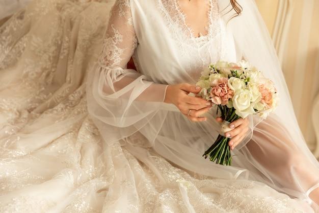 Bruid met bruiloft boeket in de buurt van trouwjurk