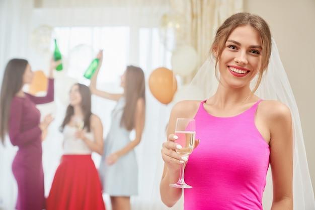 Bruid met champagnezitting bij vrijgezellinpartij.