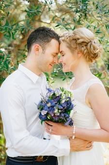 Bruid met een boeket blauwe bloemen en de bruidegom omhelst teder in de olijfgaard