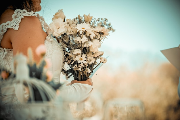 Bruid met een boeket bloemen en trouwjurk natuur en bruiloft