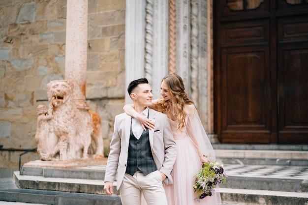 Bruid met een boeket bloemen hugs schouders van lachende bruidegom op de trap bij de ingang van de