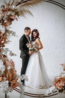 Bruid met een boeket en bruidegom op de achtergrond van de huwelijksboog