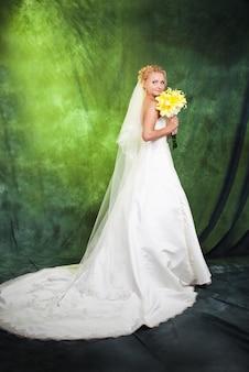 Bruid met een boeket gele lelies.