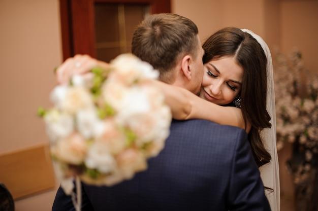 Bruid met een boeket omhelst bruidegom, terwijl hij haar kust