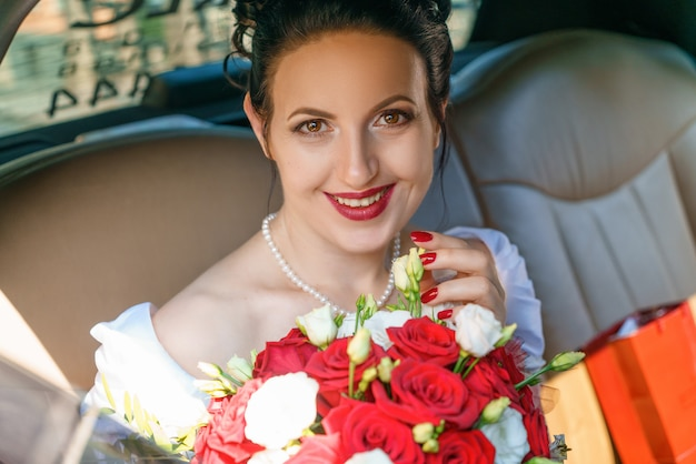 Bruid met een boeket van bloemen die in de auto zitten