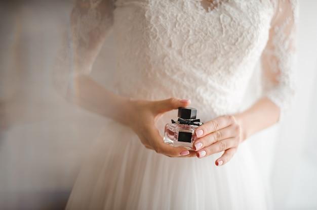 Bruid met franse manicure houdt een fles parfum