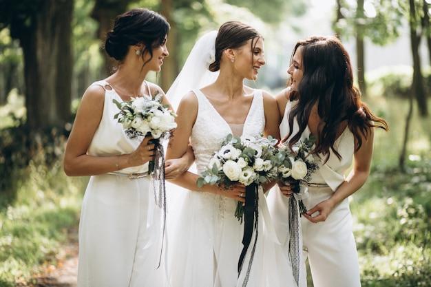 Bruid met haar bruidsmeisjes in het bos