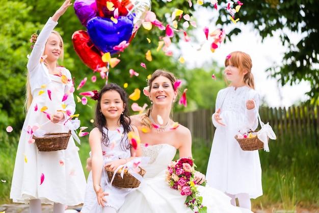 Bruid met meisjes als bruidsmeisjes, bloemen en ballonnen
