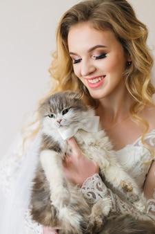 Bruid met mooi kapsel en make-up houdt pluizige kat met vlinderdas-glimlach