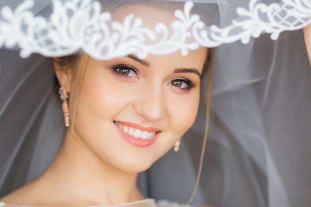 Bruid met mooie make-upglimlachen. bruidssluier met patroon.