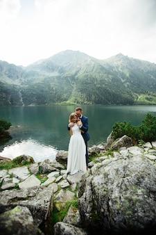 Bruid met mooie witte jurk en bruid met uitzicht op prachtige groene bergen en meer met blauw water