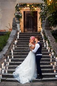 Bruid met roze haar en stijlvolle bruidegom staan op voetstappen met glanzende kaarsen