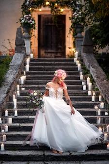 Bruid met roze haar en tatoeages op haar tedere schouder staat op voetstappen met glanzende kaarsen