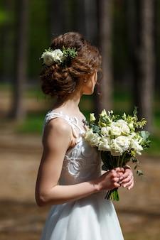 Bruid met witte natuurlijke bloemen in haar haar en huwelijksboeket in bos