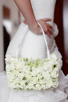 Bruid met witte trouwjurk en bloemen tas