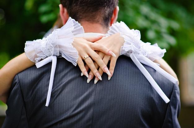 Bruid omarmt de nek van de bruidegom