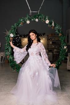 Bruid op de achtergrond van nieuwjaarslichten, kerstinterieur