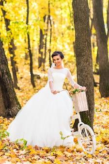 Bruid op een fiets in de herfst de natuur
