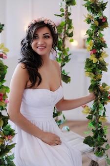 Bruid op een schommel met bloemen
