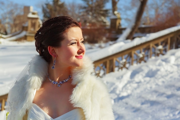 Bruid poseren in het bos van de winter in een bontjas. trouwfotosessie in een besneeuwd park. Premium Foto