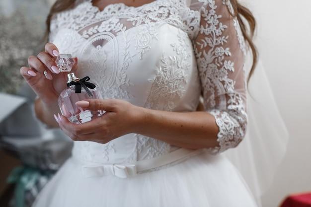 Bruid spray parfum close-up. stijlvolle bruid draagt een witte jurk spray tedere parfum. stijlvolle roze glazen fles parfum in handen close-up. ochtend bruid. bruiloft details.