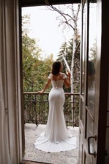Bruid staat met haar rug in een witte trouwjurk op het balkon
