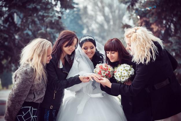 Bruid toont de trouwring aan vriendinnen