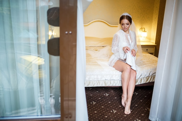 Bruid trekt witte schoenen aan op de trouwdag