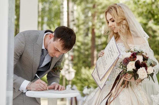 Bruid vrouw en bruidegom registreren hun huwelijk. bruiloft in de natuur. liefde voor altijd