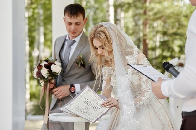 Bruid-vrouw en bruidegom registreren hun huwelijk. bruiloft in de natuur