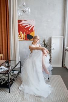 Bruid vrouw in een lichte zomer trouwjurk zitten bij het raam en wachten op de huwelijksceremonie
