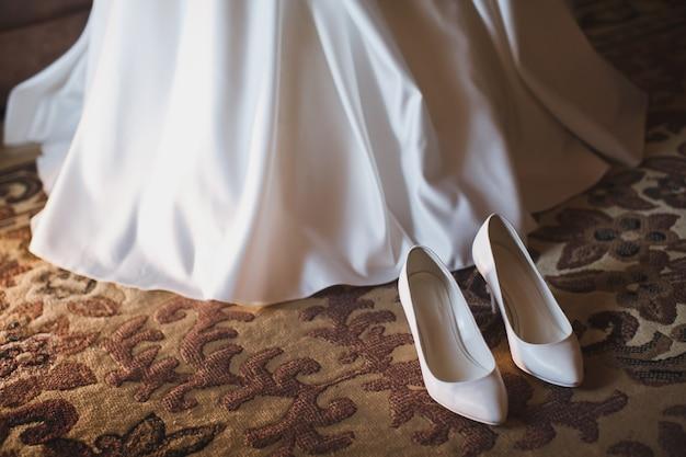 Bruid zet op witte schoenen op voeten