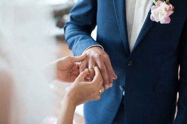 Bruid zet ring op de vinger van de bruidegom