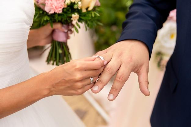 Bruid zet trouwring op bruidegom vinger