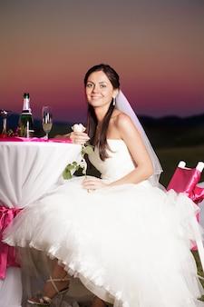 Bruid zit buiten aan de bruiloftstafel met champagne en bloem in de avondgloed
