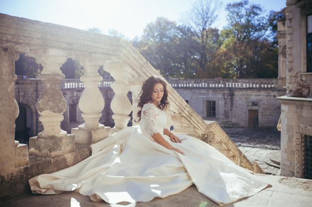 Bruid zit op de trappen van een romantisch kasteel bij zonsondergang