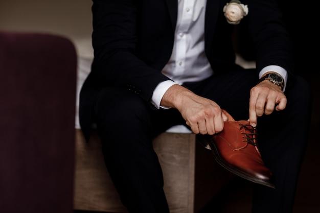 Bruidegom bond de veters dicht op de schoenen. zakenman hangt schoenen indoor in hotelkamer. mans handen en paar leren herenschoenen. bijeenkomst van de bruidegom. zakenman ochtend.