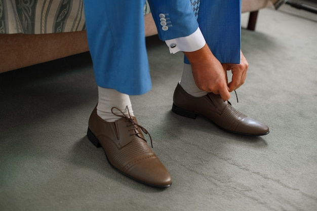 Bruidegom bond de veters op de bruine schoenen dicht omhoog. zakenman hangt schoenen binnenshuis in hotelkamer in de ochtend .. mans handen en lederen herenschoenen. vergadering van de bruidegom.