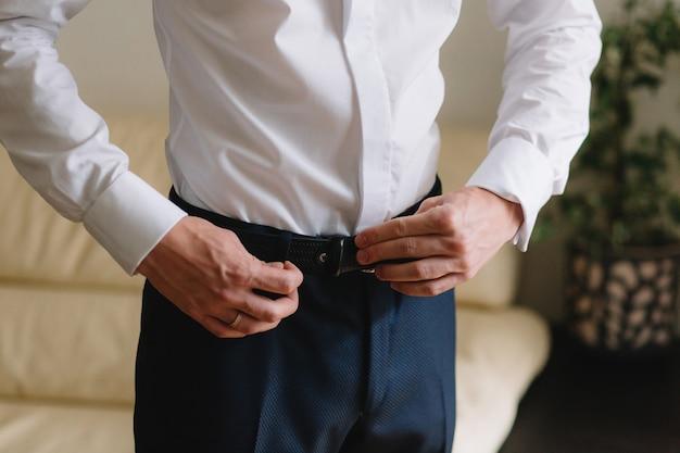 Bruidegom bruiloft ochtend voorbereiding. jonge en knappe bruidegom aankleden in een bruiloft shirt.