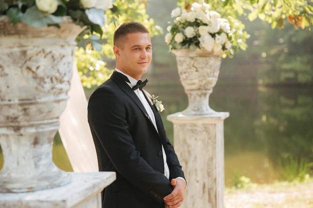 Bruidegom die bij de versierde boom staat en op de bruid wacht