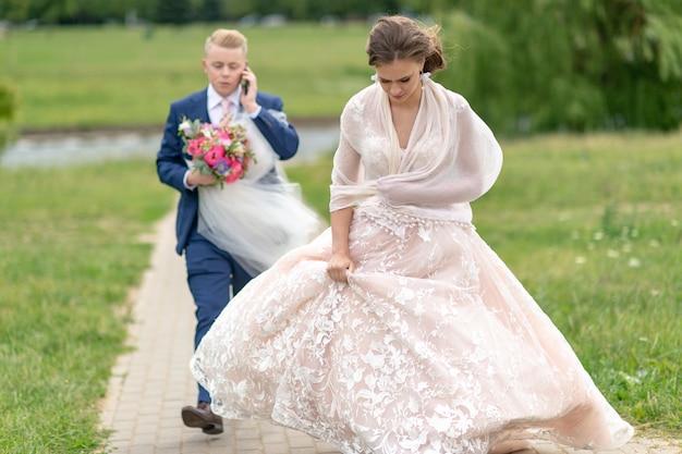 Bruidegom die bruidssluier dragen en door smartphone spreken.