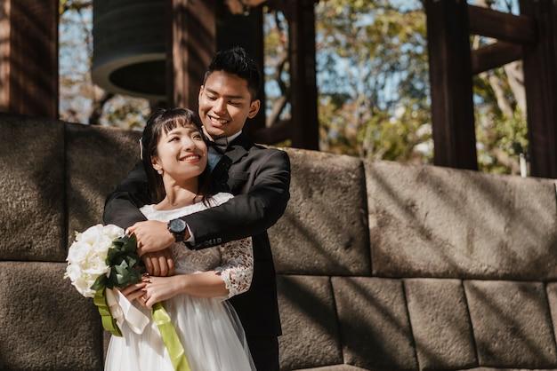 Bruidegom die de bruid met boeket bloemen buiten houdt