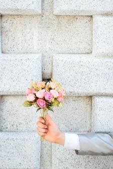Bruidegom die een boeket van roze roze bloemen en concrete muurachtergrond houdt.