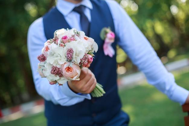 Bruidegom die een huwelijksboeket in openlucht houdt. bruidsboeket van witte rozen en pioenrozen.