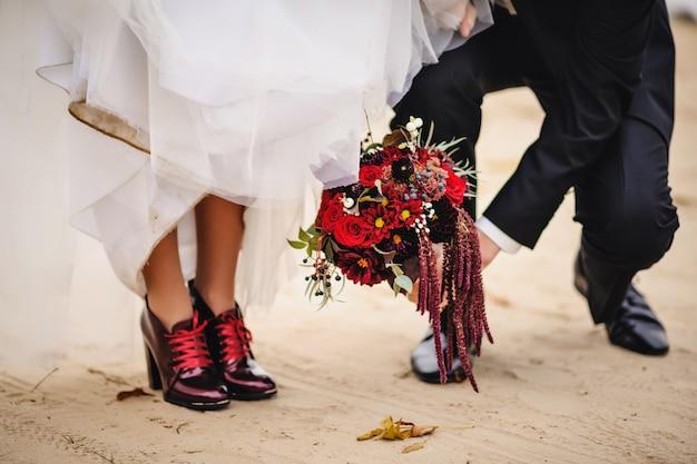 Bruidegom die een huwelijksboeket van bloemen in hand houdt