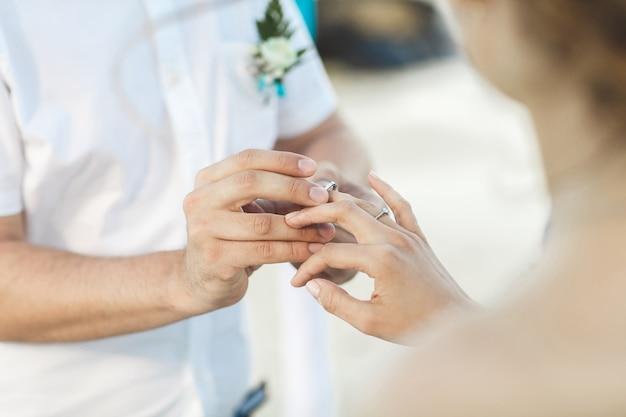 Bruidegom die een ring op de vinger van de bruid zet tijdens huwelijksceremonie