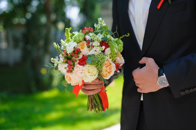 Bruidegom die in kostuum mooi bloemenboeket houdt