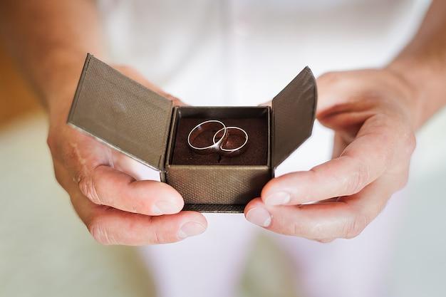 Bruidegom die mooie doos met trouwringen houdt