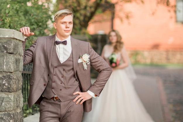 Bruidegom die op zijn bruid wacht die zich op stadsstraat bevindt. vakanties en evenementen