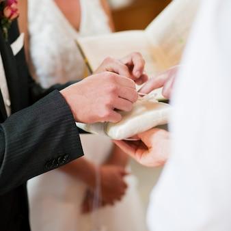 Bruidegom die ringen in huwelijksceremonie neemt